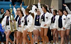 Clad in their white national champion jackets, the cheerleaders parade their trophy before the student body during a pep rally on Feb. 12. During the pep rally, they also performed their winning routine before the national championship banner was unveiled.