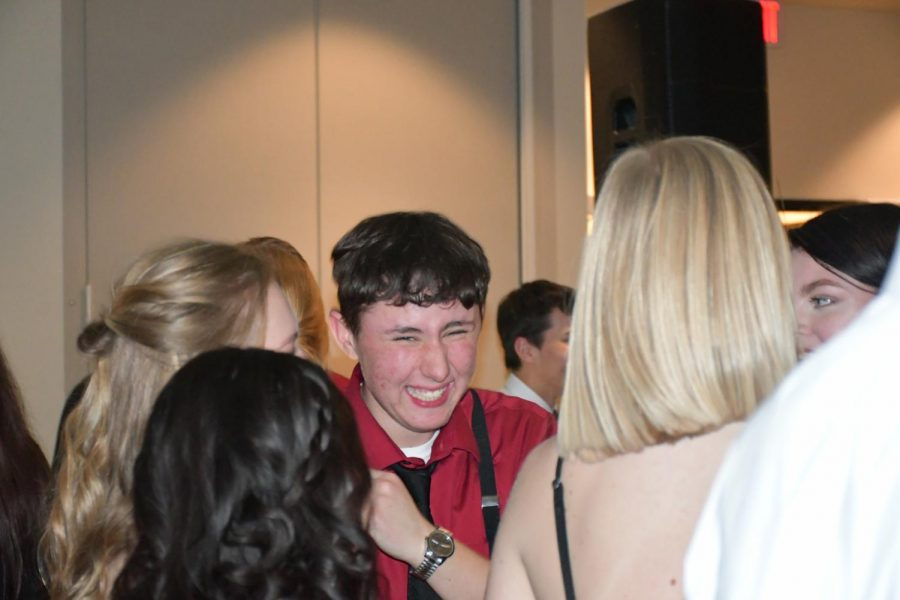 Senior TJ Rowley smiles with friends at the Senior Dinner Dance on 1/26/19