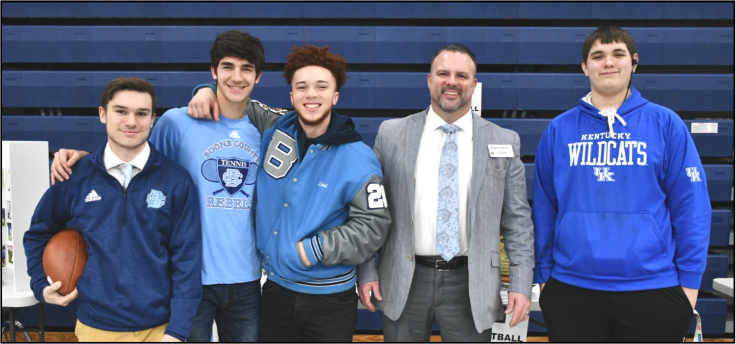 """(FROM LEFT TO RIGHT) Juniors Brice Lovell, Adam Hicks, Eli Rossi and Lance Huff stand with new football coach Bryson Warner (SECOND FROM RIGHT) during the """"Why Boone Showcase"""" on Feb. 13."""