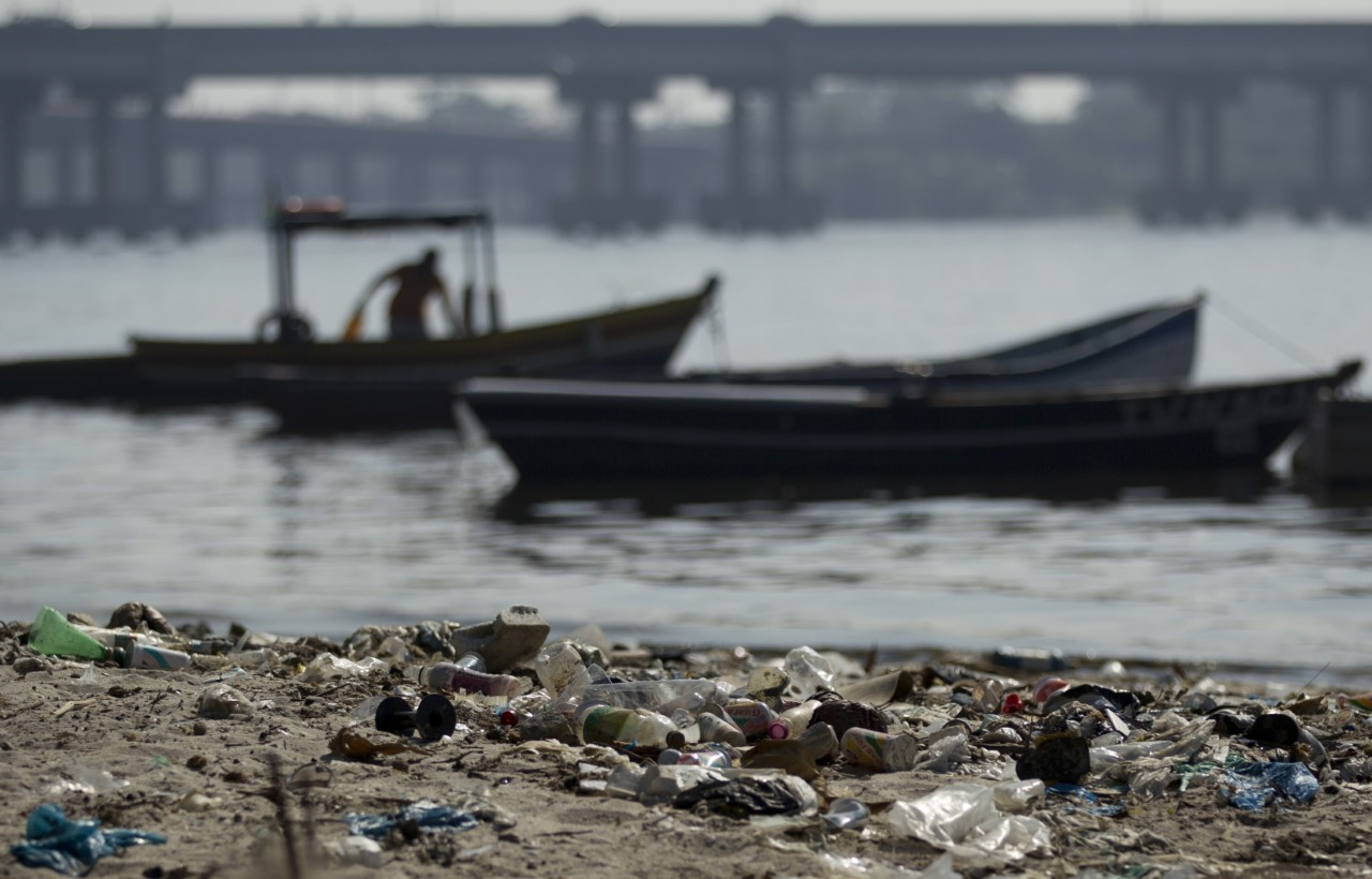 In this photo taken on Friday, June 15, 2012, a fisherman takes his boat onto a trash-ridden beach on Guanabara Bay near the international airport in Rio de Janeiro, Brazil.