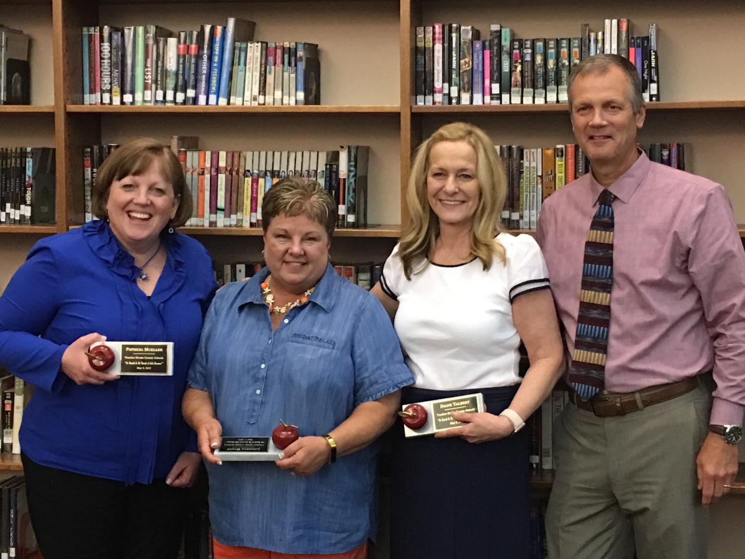 (Left to right) Retirees Patty Mueller, Louanna Wyatt, and Diane Talbert stand with principal Tim Schlotman during the annual retirees reception on May 9 in the Boone library.