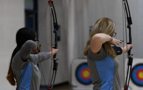 Junior Rosemary Bryant shoots alongside junior Angel Delaney at the archery tournament at Boone County High School on Jan. 11.