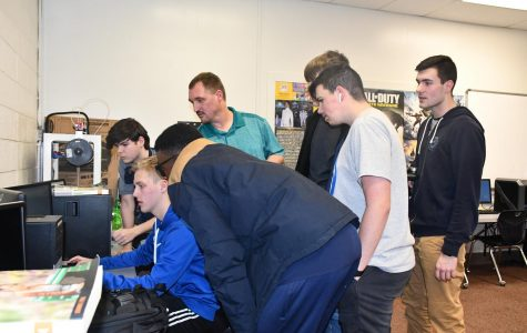 The Esports team gathers around to support Senior Brendon Hughes during the first ever esports match on Feb. 20 in room 220.