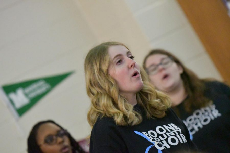 Senior Casey Beusterien sings with the choir during the arts showcase at Boone Legacy Night on Feb. 12.
