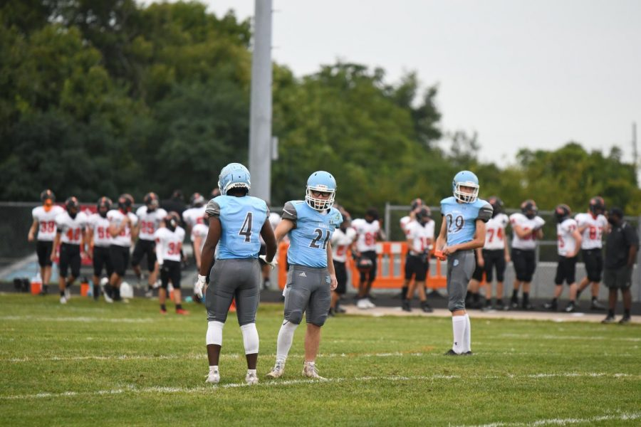 Senior Kam Anderson (21) and junior Maury Kenny (4) prepare for senior Chris Cropper's kick off before the home football game against Ryle on Sept. 11.