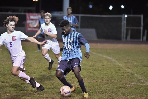 Senior Mardoche Matumueni dribbles the ball during Boone