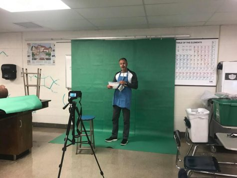 Principal Tim Schlotman is recorded in front of a green screen in room 227 for the Principal