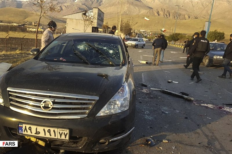 Officials move about the scene of Iranian scientist's vehicle after he was shot outside of his car in Tehran, Iran on Friday, Nov. 27.
