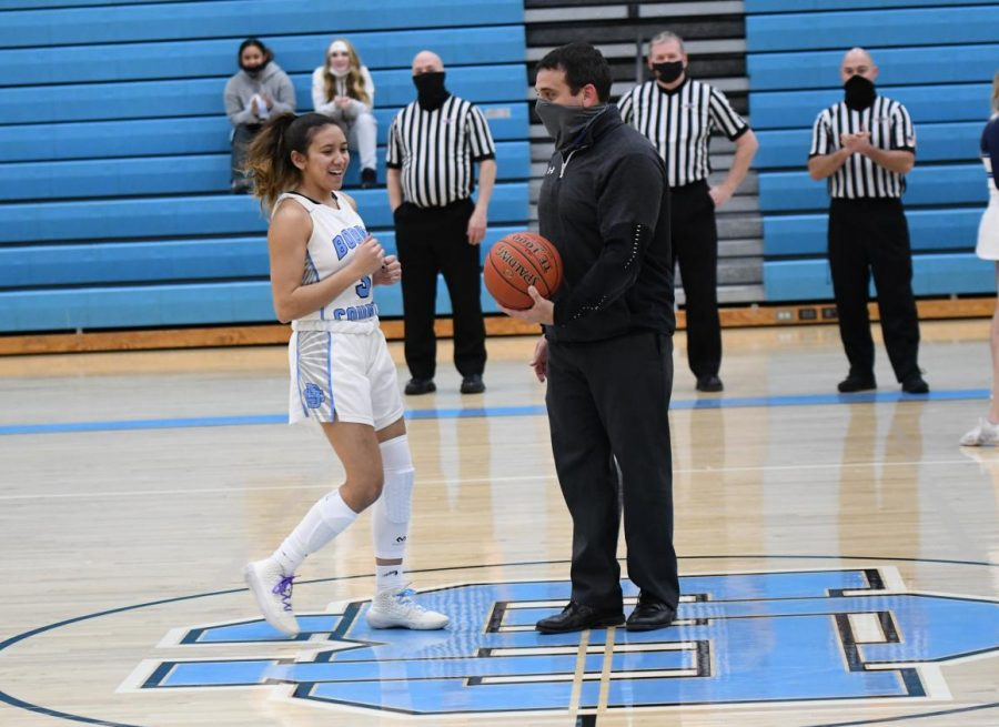 Senior Skylar Holder is presented with a game ball by coach Ryan Bowman after breaking the schools all-time steals record before the varsity basketball game against Ryle High School on Jan. 22.