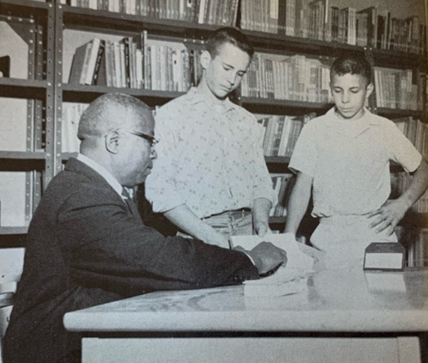 Wallace Strader, Boone's first black staff member, is pictured in an early yearbook checking out books to two students.